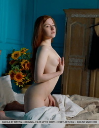 Youthful redhead Anicka shows her shaved cooch in the nude on sofa