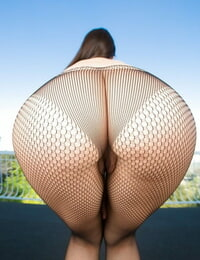 Pantyhose wearing Valentina Nappi disrobing to bare her wooly muff outside
