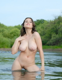 Chesty white sweetheart Paloma poses half submerged in a sea