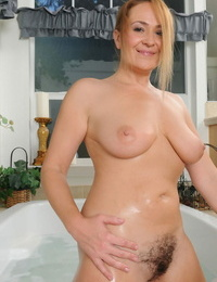 Over 30 lady with crimson hair Elexis Monroe sinks her great figure into a bathtub