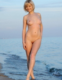 Gorgeous ash-blonde Olina D washes beach sand off warm assets in the ocean