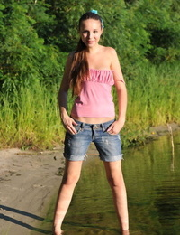 White teenage takes off jeans cut-offs to showcase her mouth to mouth beaver on beach sand