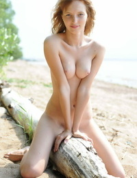 Solo girl Eriska A poses in the bare on a washed up log on the beach