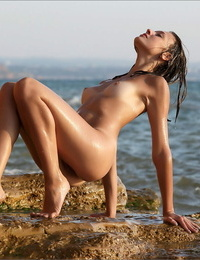 Pretty lady with pert knockers uncovers her suntan lined figure on rocks in the ocean