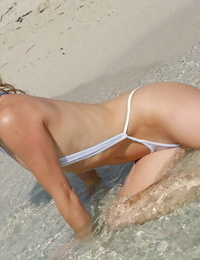 Thin girl models at the beach in a see through sling bikini and sunglasses