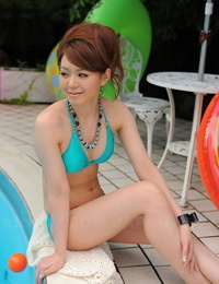 Japanese bikini model shows her pretty face while lounging by an outdoor pool