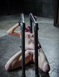 Bare redhead Ivy Addams sports cane marks on her ass while in restrain bondage