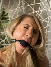 Bare blonde chick fights against ball gag and rope bindings