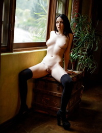 Dark haired girl peels off to seized over the knee socks in front of a window