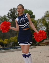 Teenage cheerleader Dani Daniels pulls up her micro-skirt to toy her gloryhole