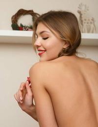 Beautiful girl Monika Dee slips off Xmas themed subjugation for bare poses in socks