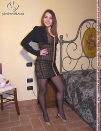 Clad lady models on her couch in a skirt and back seam tights