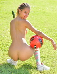 Skinny teenage sits on a soccer ball in park while inserting a cucumber in her cooch