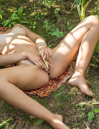 Young dark-haired Oxana Chic attends to her naughty pussy on floor of cornfield