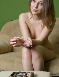 Pretty face Nikia relaxes with a candle and pets her juicy nude assets
