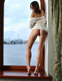 Long legged woman removes her knit sweater to model nude in a harbor doorway