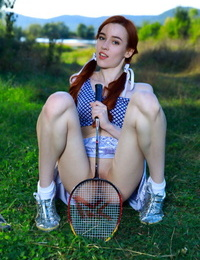 Youthfull redhead Sherice pauses a badminton game to show her tight photos on grass