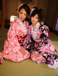 A pair of Japanese Geishas model together in their brightly colored kimonos