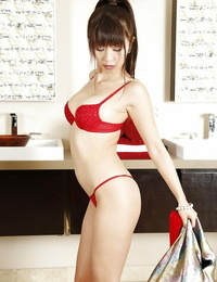 Graceful asian bombshell in high high-heeled shoes sliding off her gown and lingerie