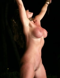 Buxomy girl is limited in the nude before being caned in the backyard