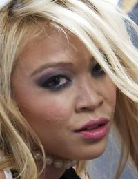 Ash-blonde Asian Mia Lelani posing in white stripper boots with gun in hand