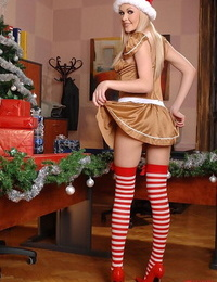 Light-haired stunner demonstrates off stocking clad gams and booty in Christmas uniform