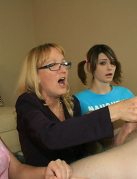 Mature blond in glasses instructing her teenager friends how to stroke a big cock