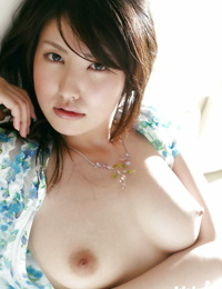 Delicious asian babe Takako Kitahara disrobing and posing on the sofa