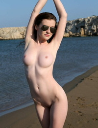 Beach sweetie Emily sunbathing naked on the sand spreading lengthy legs widely opened