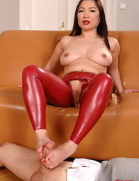 Asian stunner in latex Midori Tanaka is pleasuring a dick with a footjob