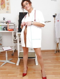 Mouthwatering mature nurse in glasses strips her panties and reveals her cunt
