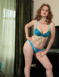 Mature redhead casts her sundress and underthings aside to show her snatch