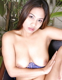 Dark-haired Asian model with fat fun bags is posing and playing