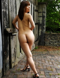 Seductive asian stunner on high high-heeled shoes showcasing her bare assets outdoor