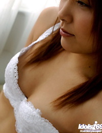Alluring asian stunner with fur covered cooter stripping on the bed