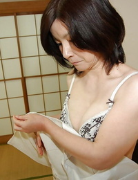 Nasty asian mature lassie getting nude and uncovering her shaggy vulva