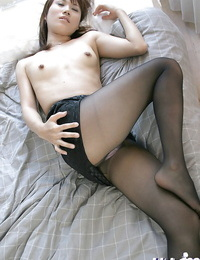 Tempting asian stunner in nylon pantyhose stripping on the sofa
