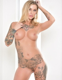 Hot solo model Kleio Valentien peels off a cat suit to pose in the bare