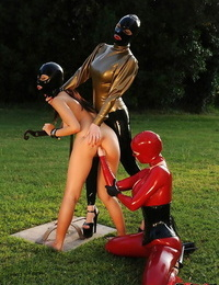 BDSM dommes in spandex suits have some fun with their female pet outdoor