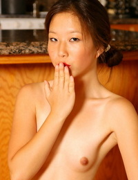 Inexperienced Asian maid strutting in kitchen in blossom and high high-heeled shoes