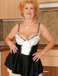 Lusty granny in maid uniform and stockings undressing in the kitchen