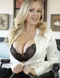 Middle-aged American woman Julia Ann uncovers her hug boobs as she strips
