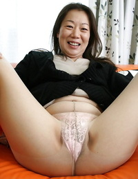 Mature brunette Yoshiko Makihara is uncovering her hairy pussy in close up