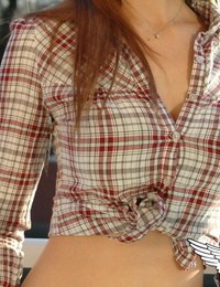 Redheaded country chick models non bare in roped up shirt and denim jeans