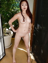 Nasty redhead Asian Lea Hart showing off her shaven cunt and posing