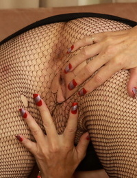 Older lady Raylynn rips open mesh tights to play with her vagina