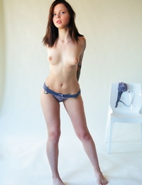 Teenage solo girl Inky removes lingerie set for mischievous nude poses