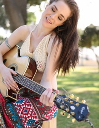 British free spirit Penny Brooks maze a breast while toying her guitar