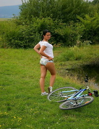 Brown-haired inexperienced rubs her bald twat against bike framework after railing into woods
