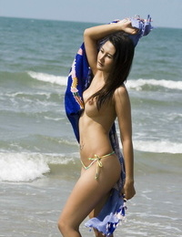 Asian amateur roams along a beach in just her bikini bottoms